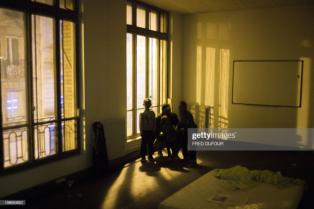 Children stand next to their father in the room they occupied in a building requisitioned by French associations 'Jeudi Noir' ('Black Thursday') and 'Droit Au Logement', ('Right to Housing Association', DAL), on January 6 , 2013 in Paris. The building, situated in the 10th arrondissement of Paris is occupied since December 31, 2012.