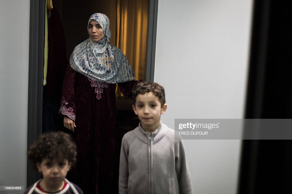 Children stand next to their mother in a corridor in front of the room they occupied in a building requisitioned by French associations 'Jeudi Noir' ('Black Thursday') and 'Droit Au Logement', ('Right to Housing Association', DAL), on January 6 , 2013 in Paris. The building, situated in the 10th arrondissement of Paris is occupied since December 31, 2012. AFP PHOTO / FRED DUFOUR