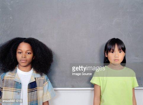 Children standing against blackboard : Stock Photo
