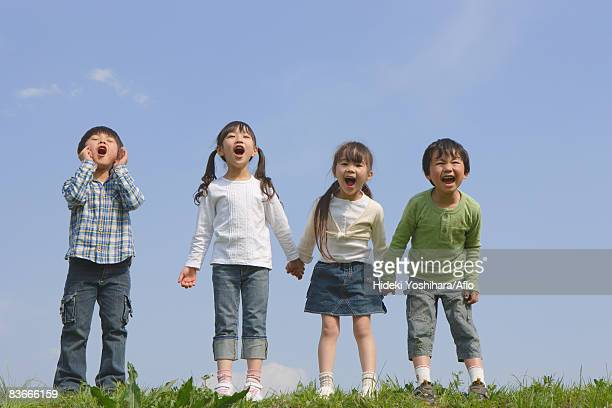 Children standing in a row and yelling together