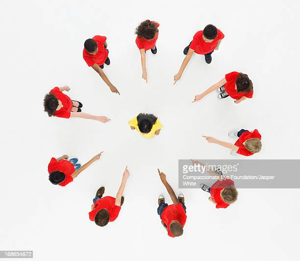 Children standing in circle pointing to centre