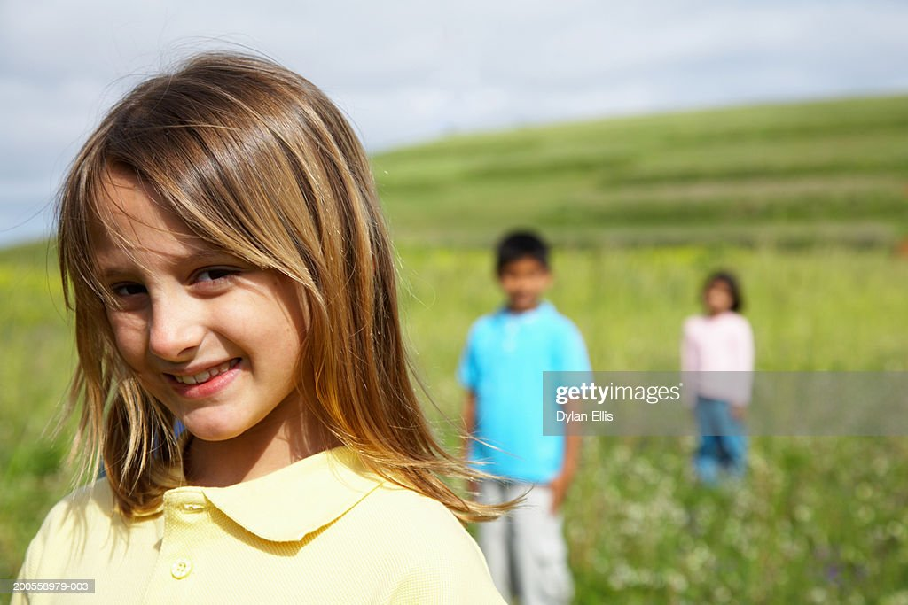 Children (6-9) standing in field, girl smiling in foreground : Stock Photo