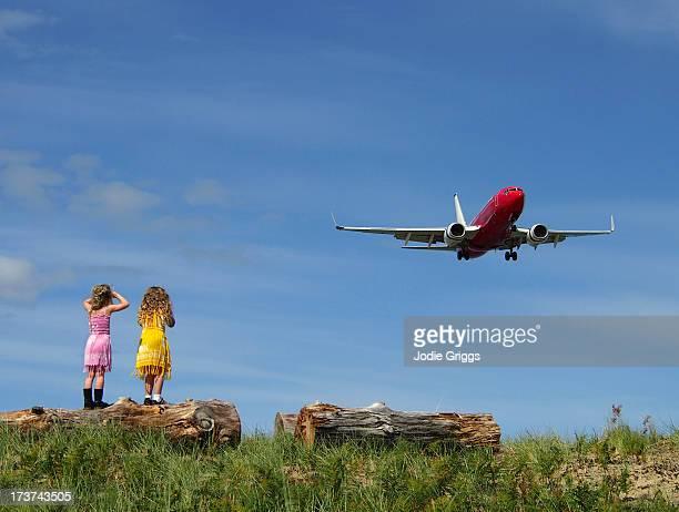 Children standing on log watching aeroplane land