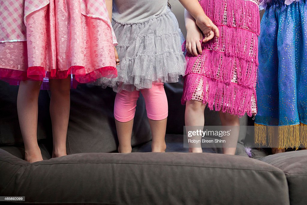 Children standing on sofa : Stock Photo
