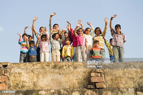 Children standing on the roof of a house, Hasanpur, Haryana, India