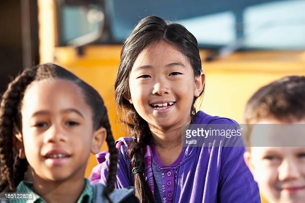 Enfants debout à l'extérieur de l'école en bus