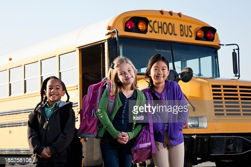 Children standing outside school bus