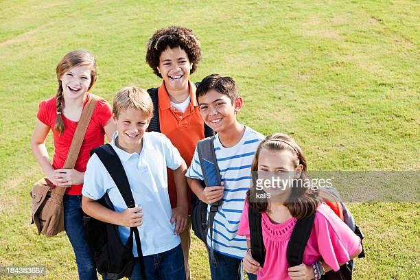 Bambini in piedi fuori scuola con cartella,
