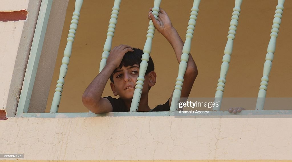 A children stares at balcony as Iraqi people in Fallujah town leave their home due to conflicts between Daesh and security forces in Anbar, Iraq on May 30, 2016. Some of the families who left their home are placed in a school in Karma Town, west of Anbar city.