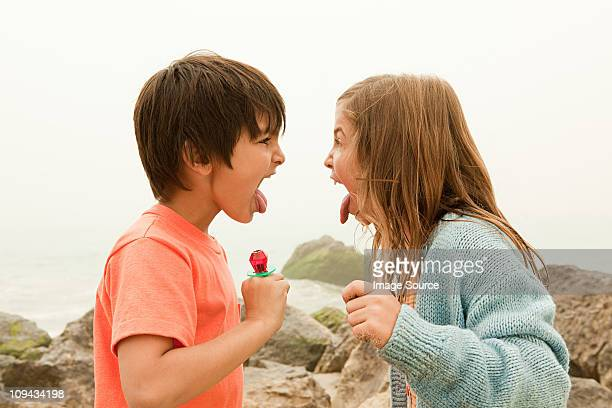 Children sticking out tongues, holding lollipops