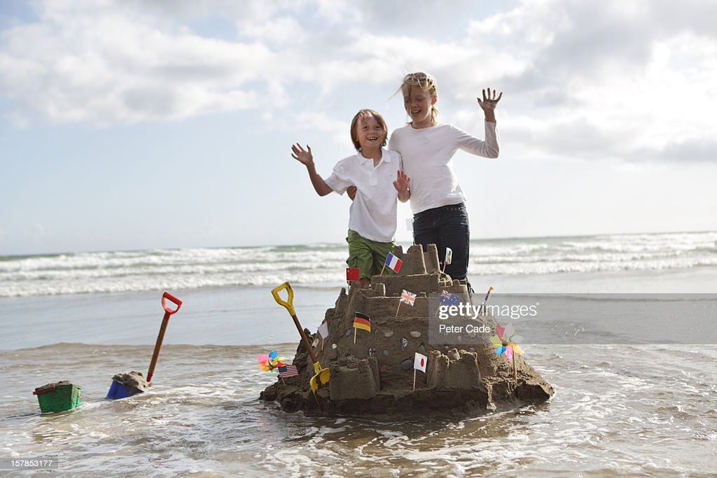 Children stood on sandcastle surrounded by water : Stock Photo