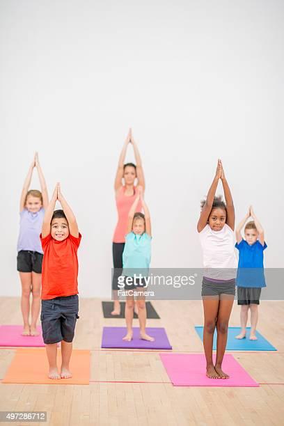 Los niños de estiramiento y plantear sus brazos en el aire