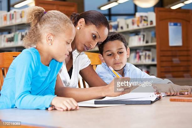 Enfants étudiant dans la bibliothèque avec professeur