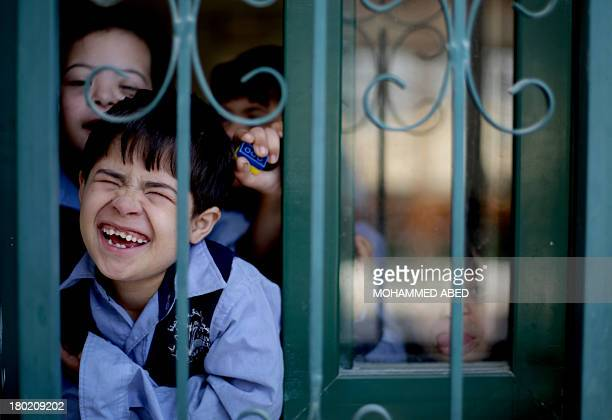 Children suffering from the Down syndrome smile behind the window of a specialised kindergarten of the 'Right to Live Society' a Palestinian...