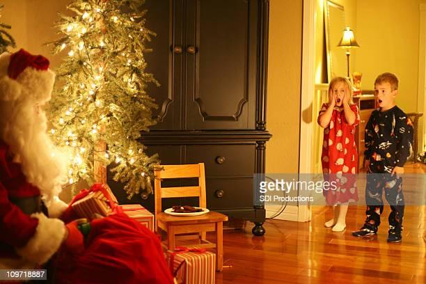 Enfants surpris de Santa est assis à la maison
