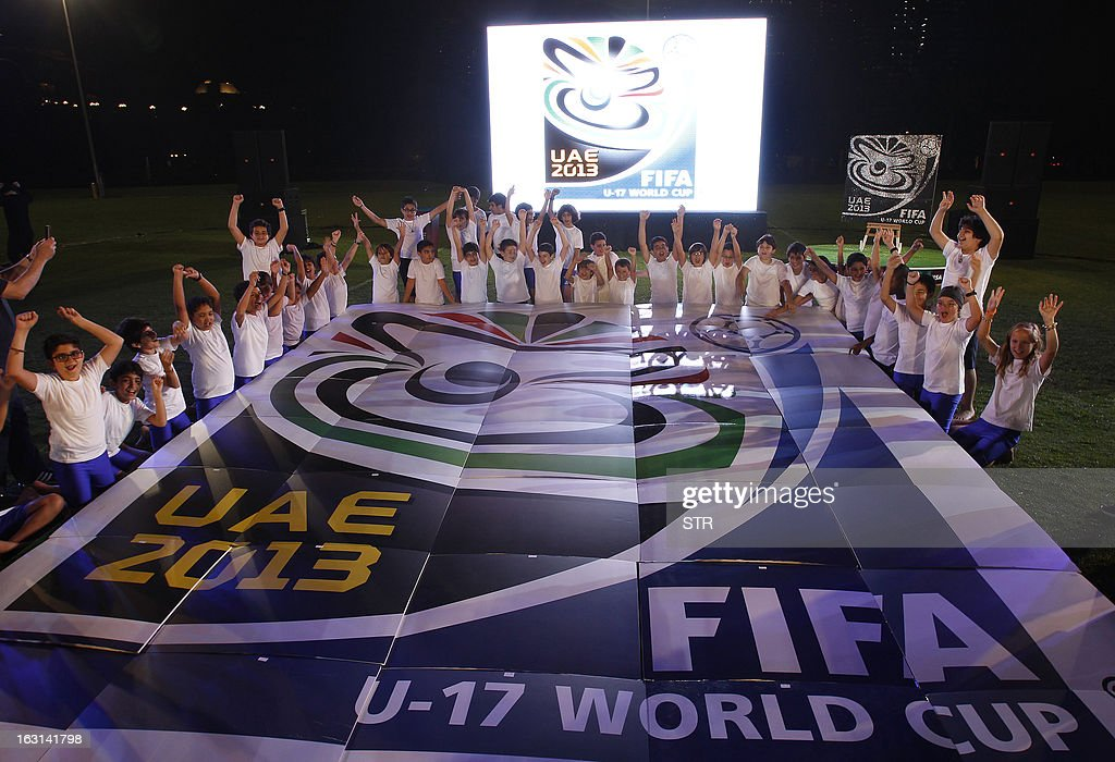 Children surround the official emblem of the FIFA U17 World Cup during an unveiling ceremony at the Emirates Palace in Abu Dhabi, on March 5, 2013. The 2013 U-17 World Cup will be held in the United Arab Emirates between October 17 and November 8. AFP PHOTO/STR