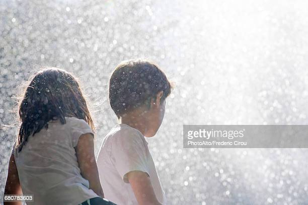 Children surrounded by spray from waterfall