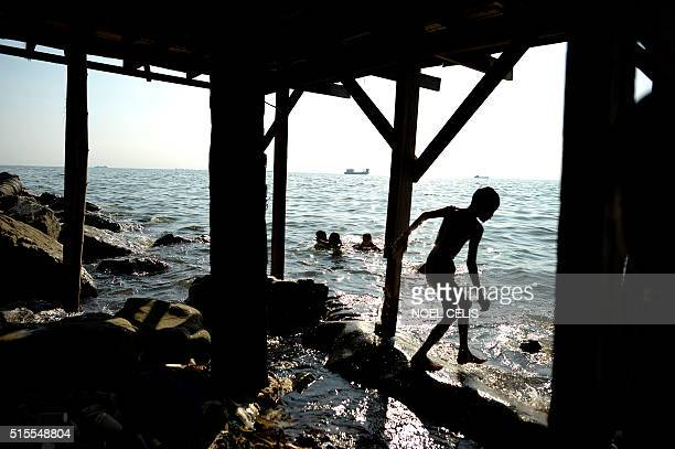 Children swim at the sea near houses constructed on the breakwater at Manila Bay on March 14 2016 Families living beside the shore are vulnerable to...