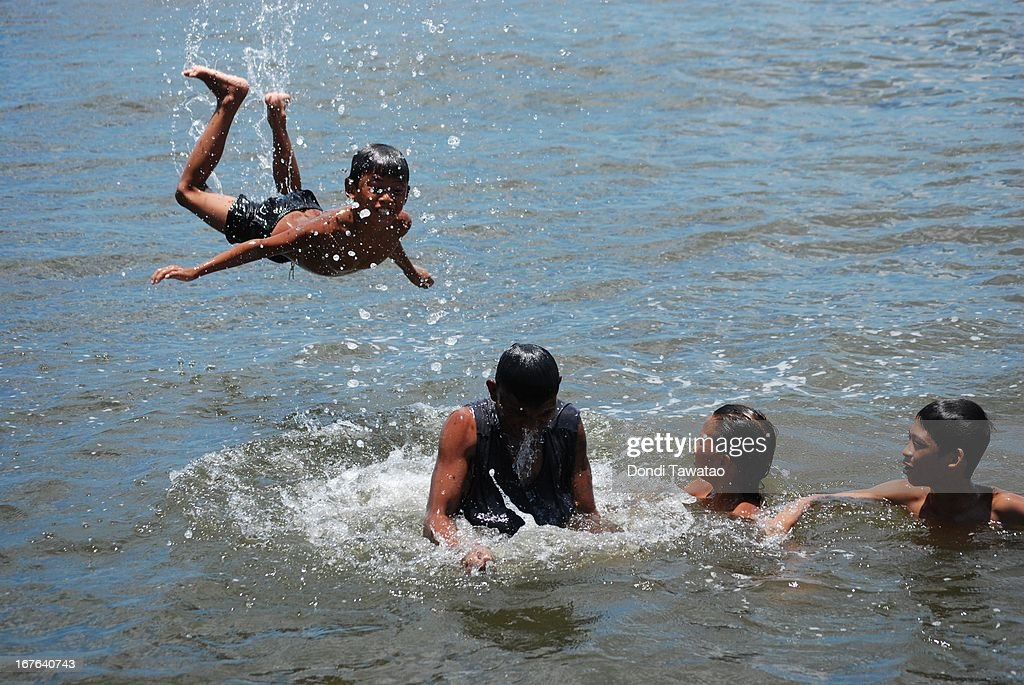 Children swim in the murky waters of Navotas de Bay on April 27, 2013 in Manila, Philippines. Despite small rainshowers, temperatures soared from 35 to 36.1 degrees in parts of the Philippines as State weather forecasters project hotter days ahead and advised residents to stay indoors during afternoon to avoid heat stroke.