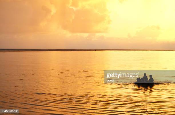 Children swimming at sunset in the Indian Ocean