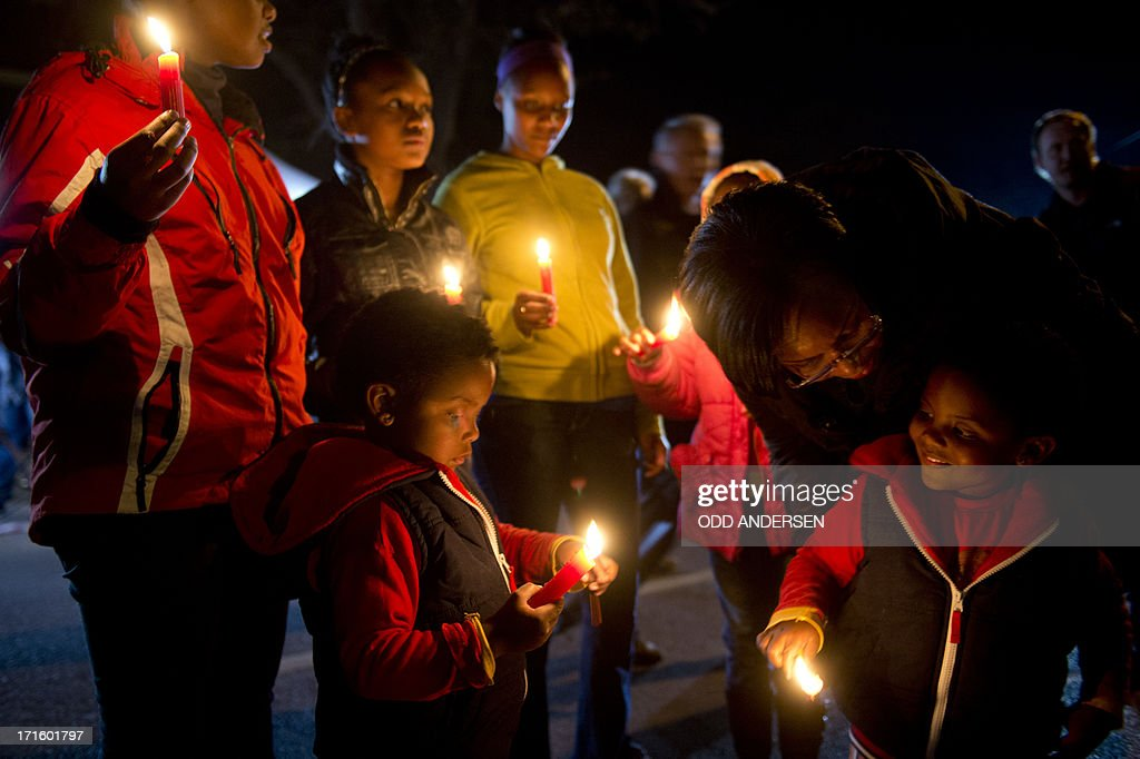 Children take part in a candle lit vigil in support of Nelson Mandela outside the Mediclinic heart hospital in Pretoria on June 26, 2013. Mandela is receiving treatment at the Mediclinic heart hospital in Pretoria. Mandela's close family gathered yesterday at his rural homestead to discuss the failing health of the South African anti-apartheid icon who was fighting for his life in hospital. Messages of support poured in from around the world for the Nobel Peace Prize winner, who spent 27 years behind bars for his struggle under white minority rule and went on to become South Africa's first black president.