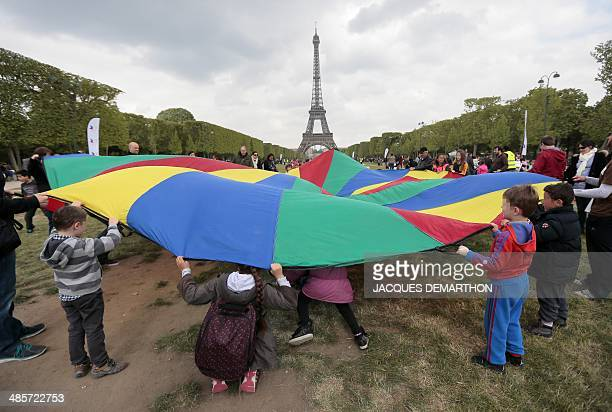 Children take part in an Easter egg hunt organised by the Secours Populaire in front of the Tour Eiffel at the ChampdeMars in Paris on April 20 2014...