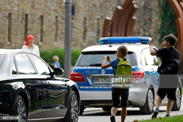Children take photos of the car leaving with German Chancellor and head of the German Christian Democrats Angela Merkel after an election rally at...