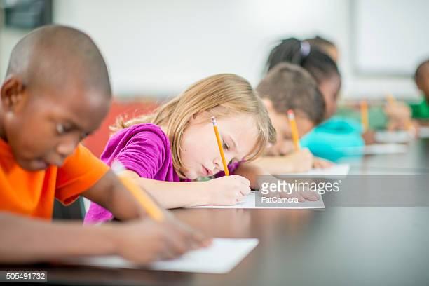 Kinder, die ein Quiz in Class