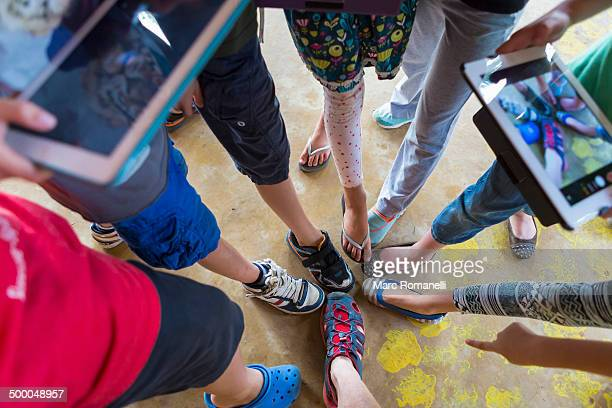 Children taking pictures of shoes with digital tablets