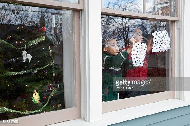 Children taping homemade snowflakes on window