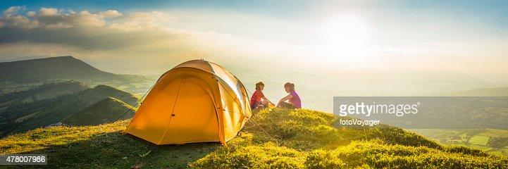 Children tent camping on idyllic summer sunset mountain top panorama
