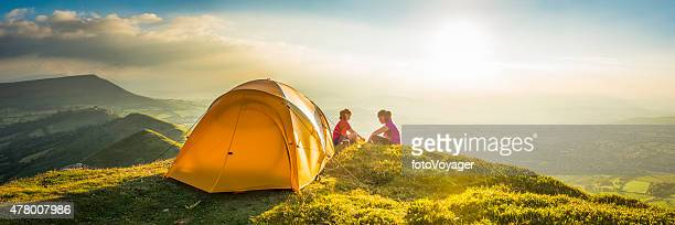 Children tent camping on idyllic summer sunset mountain top panorama