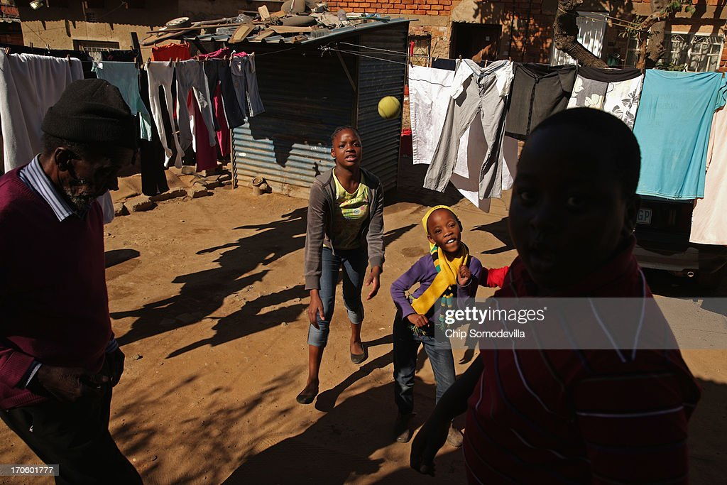 Children throw as they play ball in an alley behind shacks in the Alexandra Township June 15, 2013 in Johannesburg, South Africa. former South African President and leader of the anti-apartheid movement, Nelson Mandela is spending a seventh night in hospital and is reported to be responding better to treatment for a recurring lung infection.