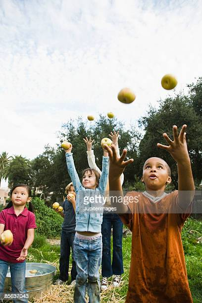 Children throwing apples into air