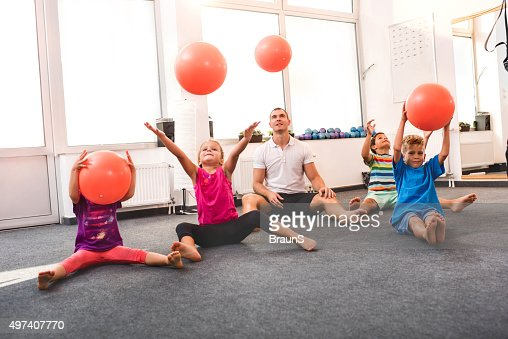 Children throwing balls on an exercise class with a coach.