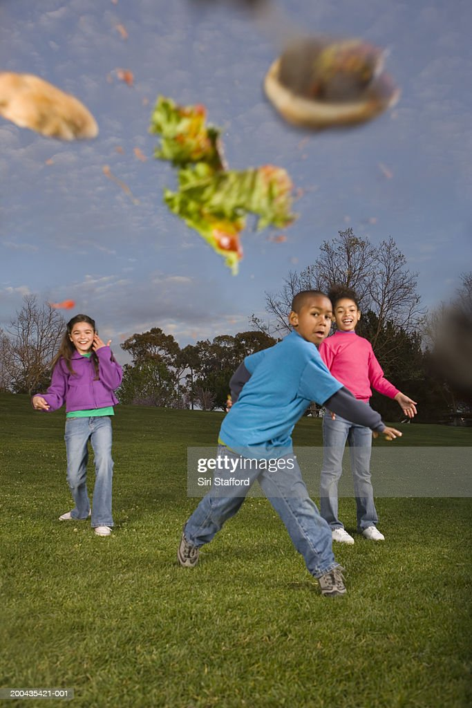 Children (8-10) throwing food : Stock Photo