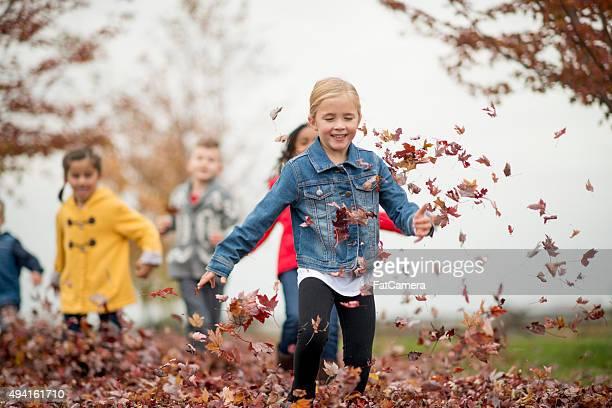 Enfants jeter les feuilles de l'automne