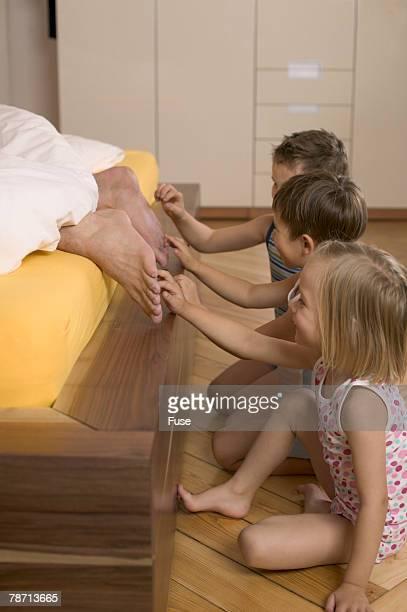 Children tickling feet of parent lying in bed