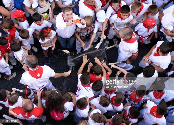 Children touch a practice bullhead prior to running the 'Encierro Txiki' during the San Fermin Festival in Pamplona northern Spain on July 13 2017...