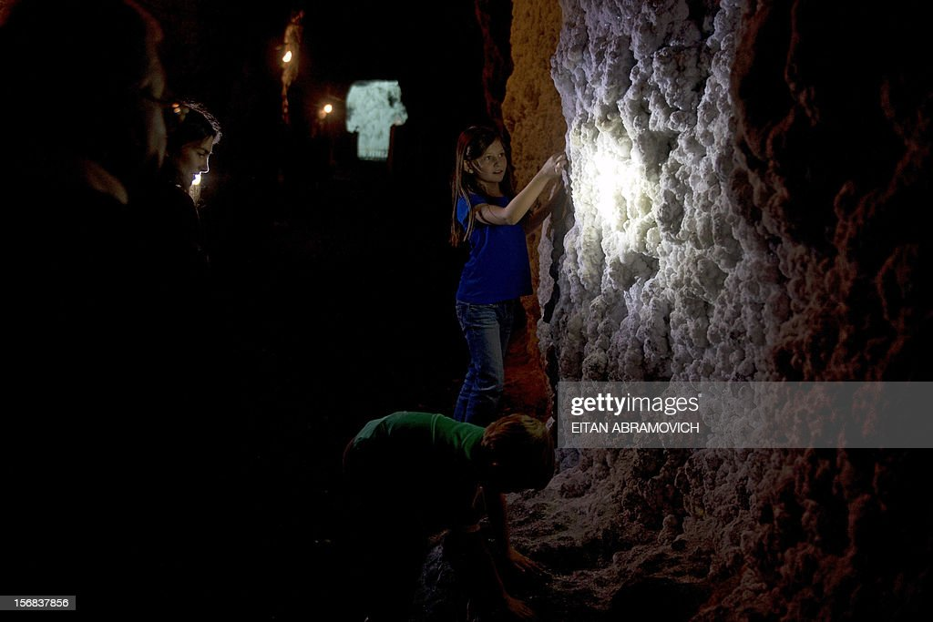 Children touch a salt wall at Nemocon's salt mine in Nemocon, Cundinamarca, Colombia on November 22, 2012. The mine, an impressive construction at 80 meters of depth with over 500 years of history, has become a new attractive tourist destination in Colombia. AFP PHOTO/Eitan Abramovich