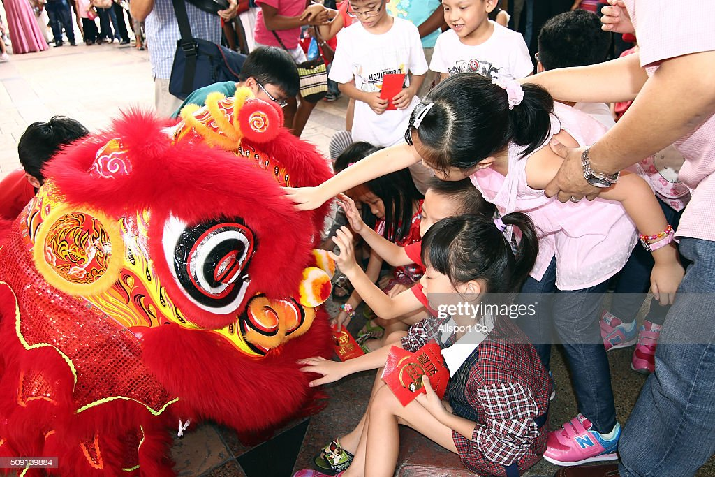Children touches a Traditional Lion Dance during performances at a shopping mall on the 2nd day of Lunar New Year celebrations on February 9, 2016 in Kuala Lumpur, Malaysia.The Chinese New Year, also known as the Spring Festival, is celebrated from the first day of the first month of the lunar year and ends with Lantern Festival on the Fifteenth day.