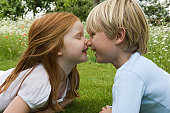 Children touching noses in field