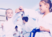 Happy children training in pairs to at karate classes