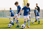 Children Training Soccer on Field. Young Kids Boys kicking Soccer Football Balls on Grass Pitch. Kids in Sportswear Practice Soccer Skills