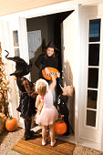 Children trick or treating getting candy at house