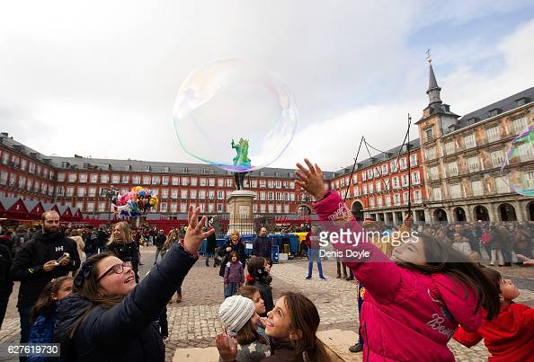 Children try to burst a soap bubble during the beginning of the annual Christmas shopping season on December 3 2016 at Mayor square in Madrid Spain...