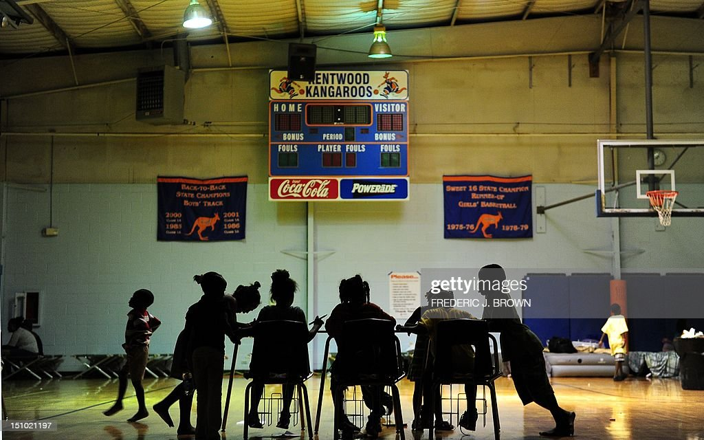 Children try to do their homework at an evacuation shelter in a high school gymnasium in Kentwood, northeast of New Orleans on August 30, 2012 in Louisiana, where Tropical Storm Isaac has dumped more rain onto an already saturated Gulf Coast leaving residents to seek safety from flooding. Authorities in two states along the US Gulf Coast urged residents to seek shelter amid fears the Percy Quin dam in Mississippi near the Louisiana border showed signs of damage due to the storm. AFP PHOTO / Frederic J. BROWN