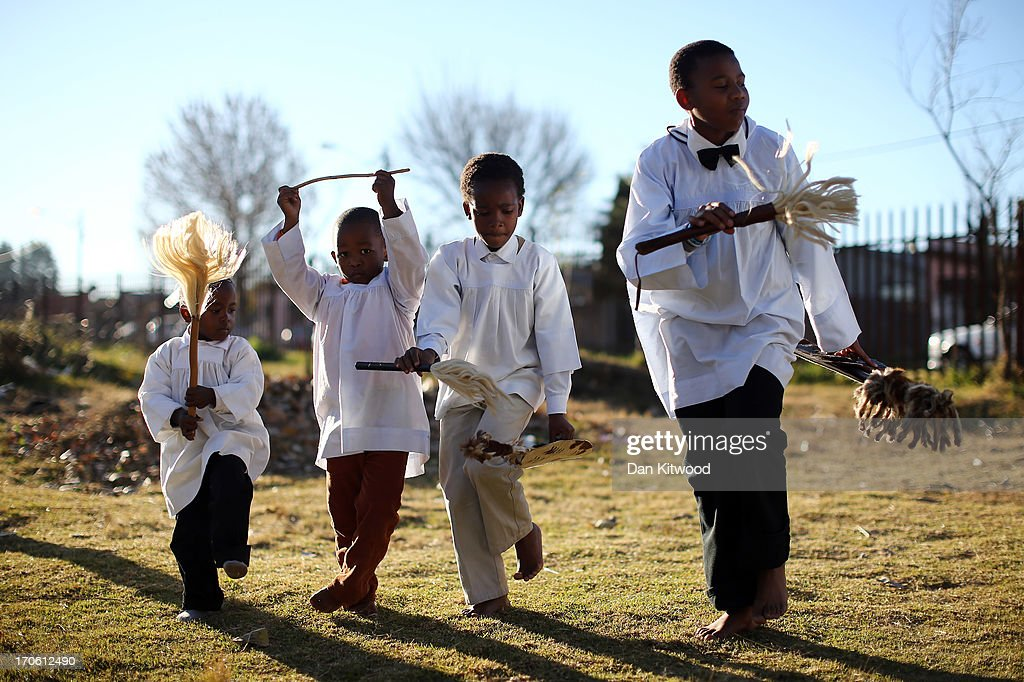 Children try to keep up with elders as members of the Church of Nazareth take part in a service at Rockville School, in Soweto on June 15, 2013 in Johannesburg, South Africa. The Baptist church, which is a mixture of Zulu tradition and Christianity, continued their daily life as the former South African President and leader of the anti-apartheid movement who is spending a seventh night in hospital. It has been reported that he is responding better to treatment for a recurring lung infection.