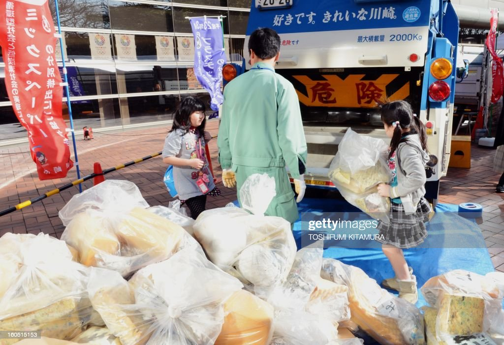 Children try to load garbage bags onto a truck during recycling lessons in the Kawasaki International Eco-Tech Fair 2013 in Kawasaki on February 2, 2013. AFP PHOTO / TOSHIFUMI KITAMURA
