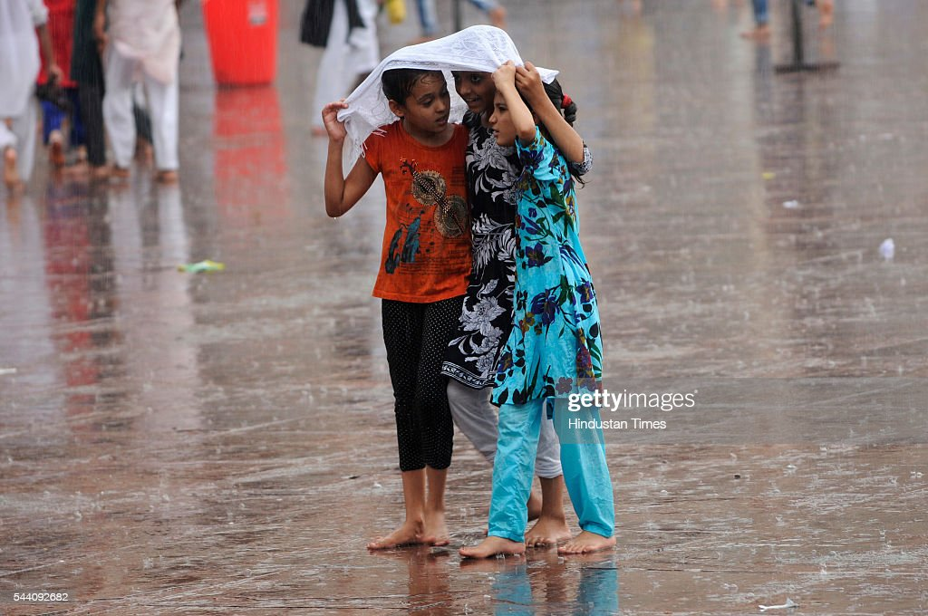 Children trying to shield themselves from rains near Jama Masjid on July 1, 2016 in New Delhi, India. The capital received its first Monsoon rains dragging the maximum temperatures several notches below normal. Heavy downpour caused water logging and traffic jams in the city.